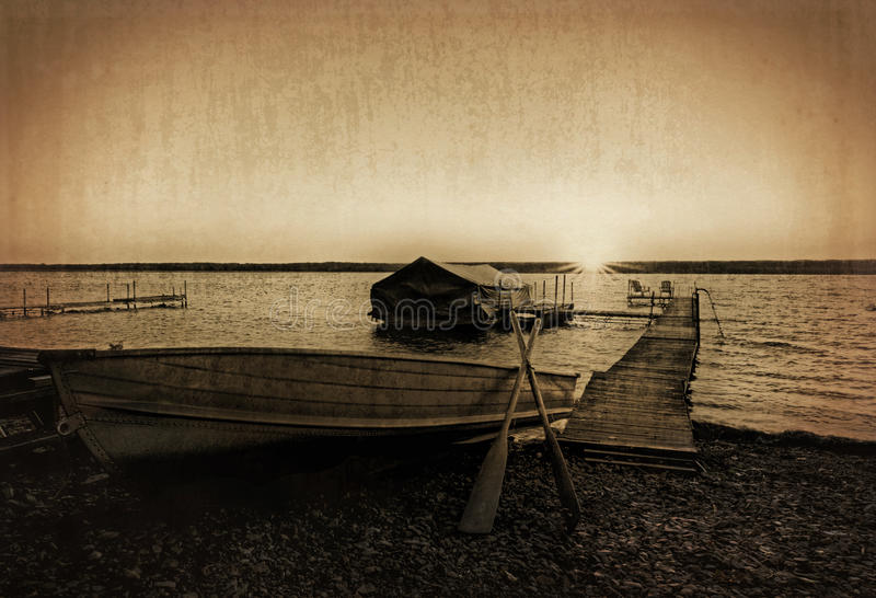 Vintage Boat Dock. Photo of a lake shore dock with a row boat and boat shelter at sunrise. Photo has been enhanced with a sepia tone an textured for a grungy royalty free stock photos