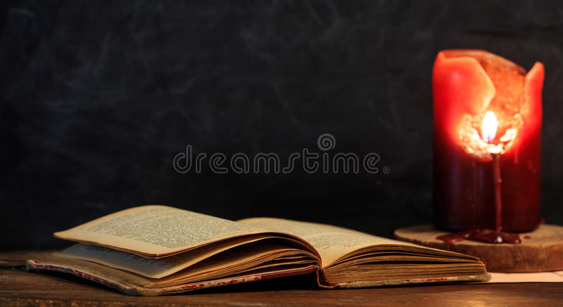 Vintage book and candle on black background royalty free stock photo