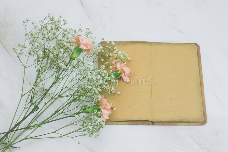 Vintage book with empty sheets and flowers on a marble background. Top view vintage book with empty sheets and flowers on a marble background stock images