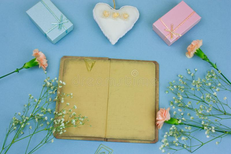 Vintage book with empty sheets , gift boxes and flowers on a pastel blue background. Top view vintage book with empty sheets , gift boxes and flowers on a pastel royalty free stock images