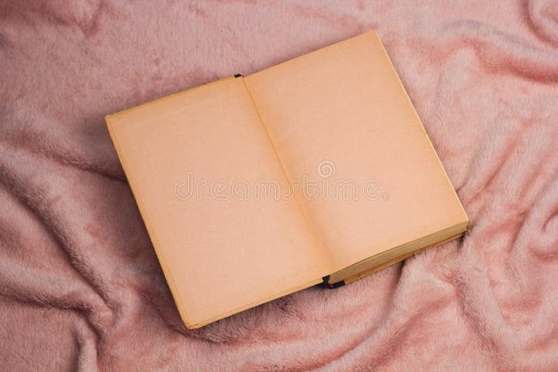 Vintage book opened empty sheets mock up. On a blanket top view stock photo