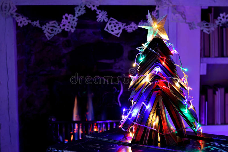 Vintage books Christmas tree and cosy open fire. Christmas tree made from vintage books with fairy lights in front of an open flame fire. With star and stock photos