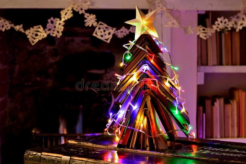 Vintage books Christmas tree, snowflake chain and open fire. Christmas tree made from vintage books with fairy lights in front of an open flame fire. With star royalty free stock images