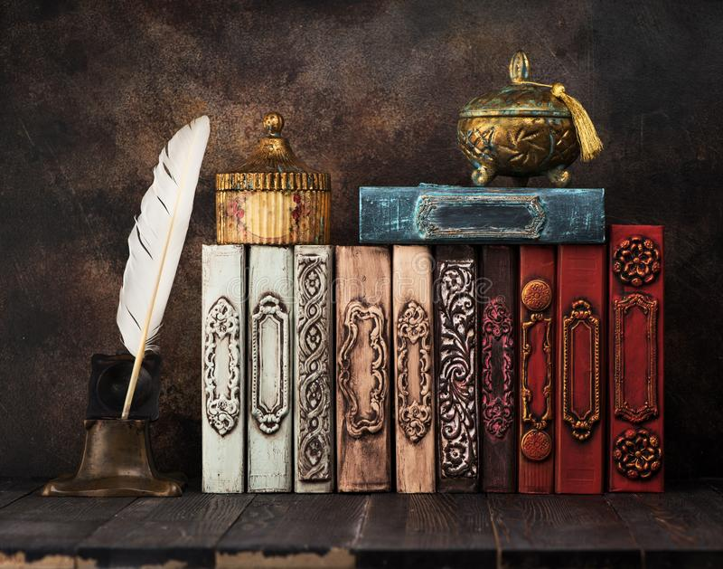 Vintage books on a shelf, ancient caskets, manuscript and antiquarian inkwell with a feather. stock photography