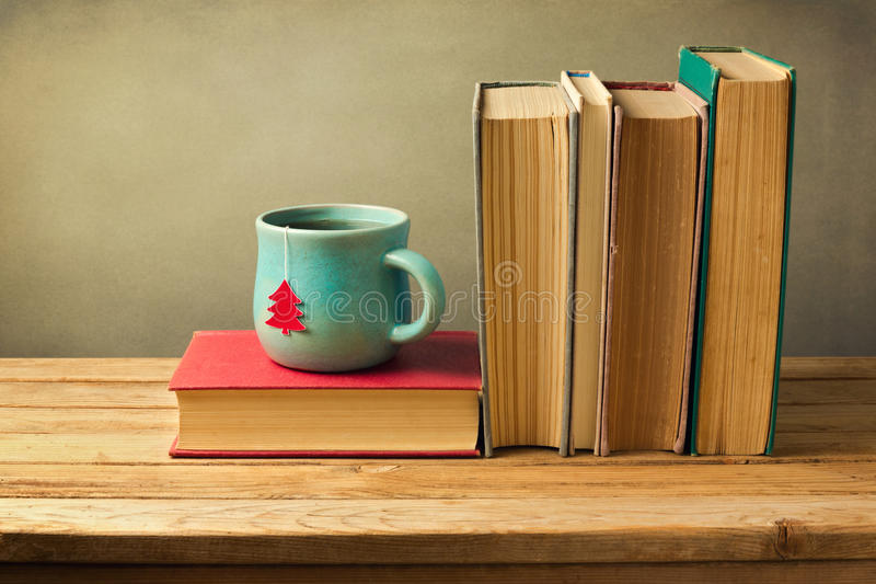 Vintage books and tea cup on wooden table. Christmas celebration. stock photography