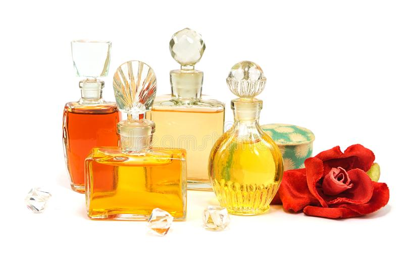 Vintage bottles of perfume with the glass stoppers, old cosmetic powder and artificial plush red rose on white royalty free stock image