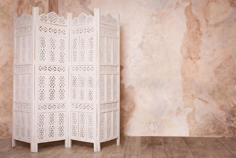 Vintage boudoir room. White delicate decorative wood panel on brown plaster wall. Boudoir wedding room. Retro folding screen. Vintage ornate carved folding stock photo