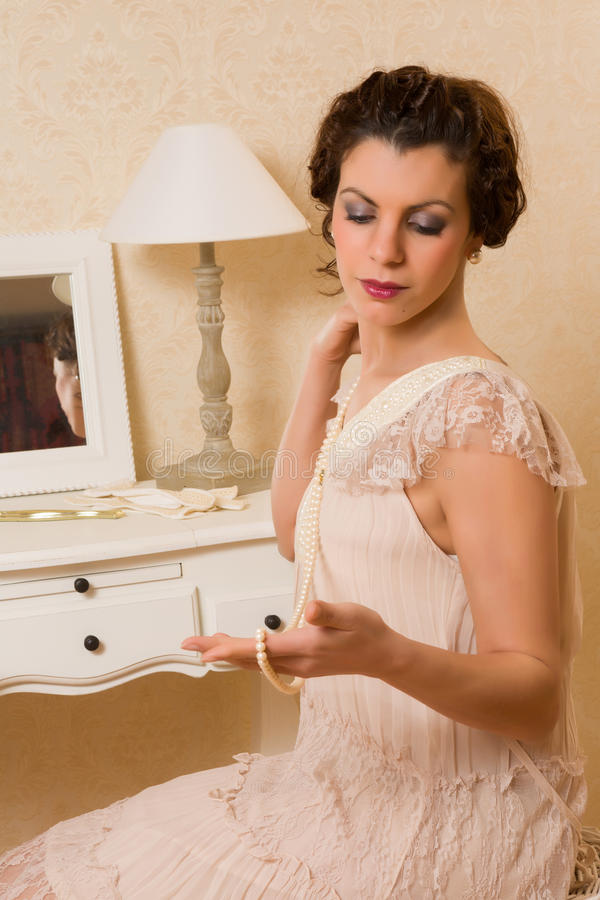 Vintage boudoir scene. Young vintage 1920s woman choosing jewelry in her boudoir royalty free stock images