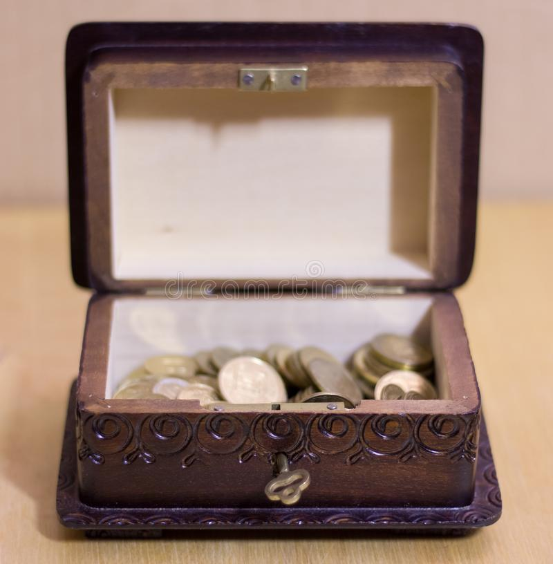 Vintage box with coins. Vintage box with different coins royalty free stock images
