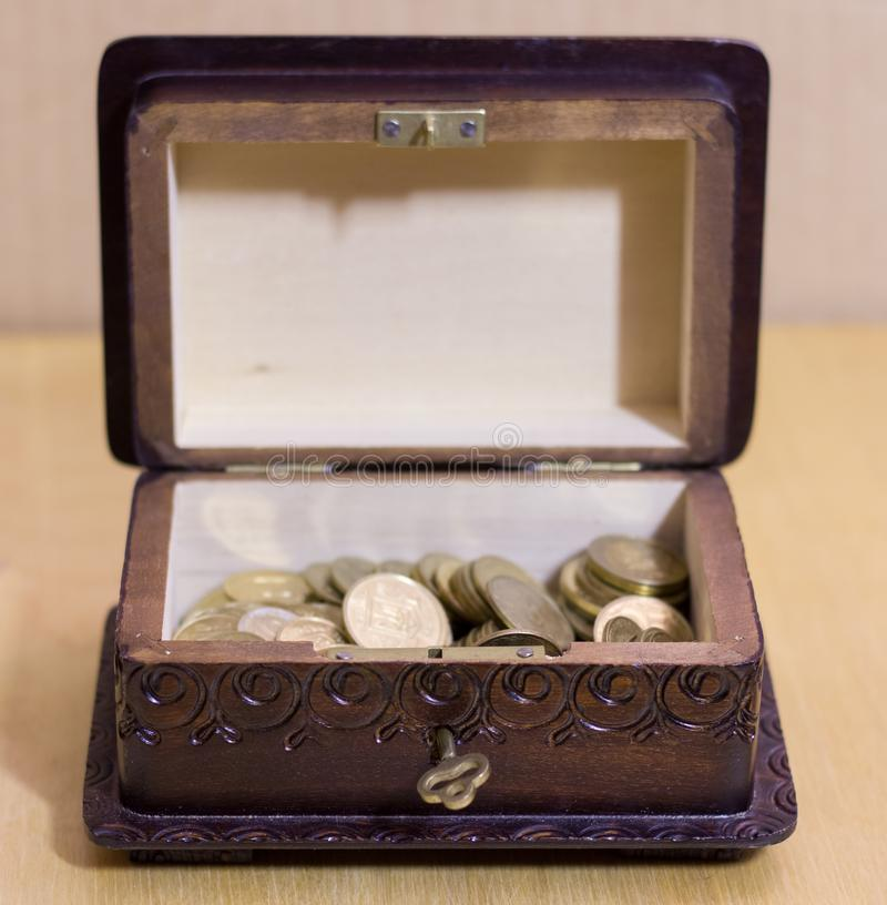 Vintage box with coins. Vintage box with different coins royalty free stock photos