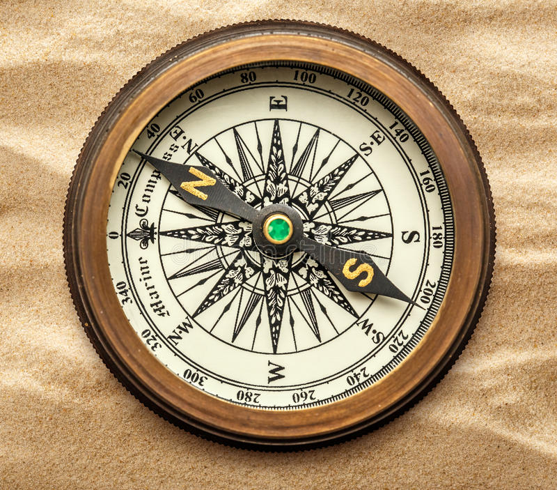 Vintage brass compass on sand stock photos