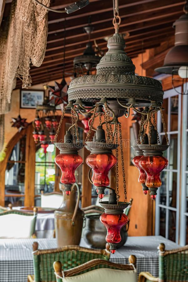 Vintage brass lamp with red glass shades hanging under a canopy. Bunch of ripe bananas and a local village in the blurred stock image