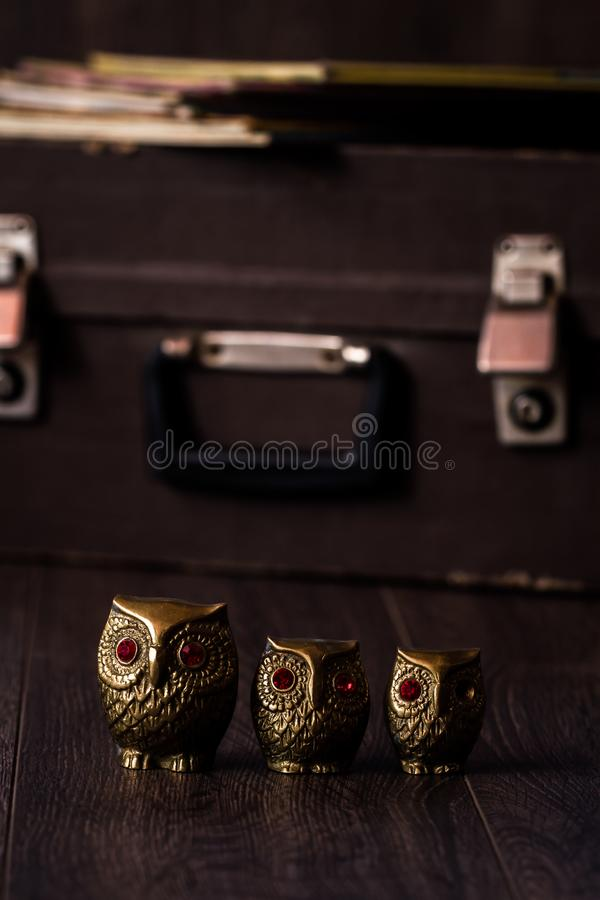 Vintage Brass Owl Figurines on Brown Wooden Background royalty free stock image