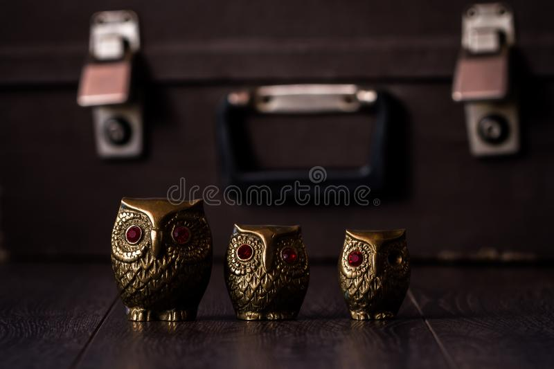 Vintage Brass Owl Figurines on Brown Wooden Background stock photo