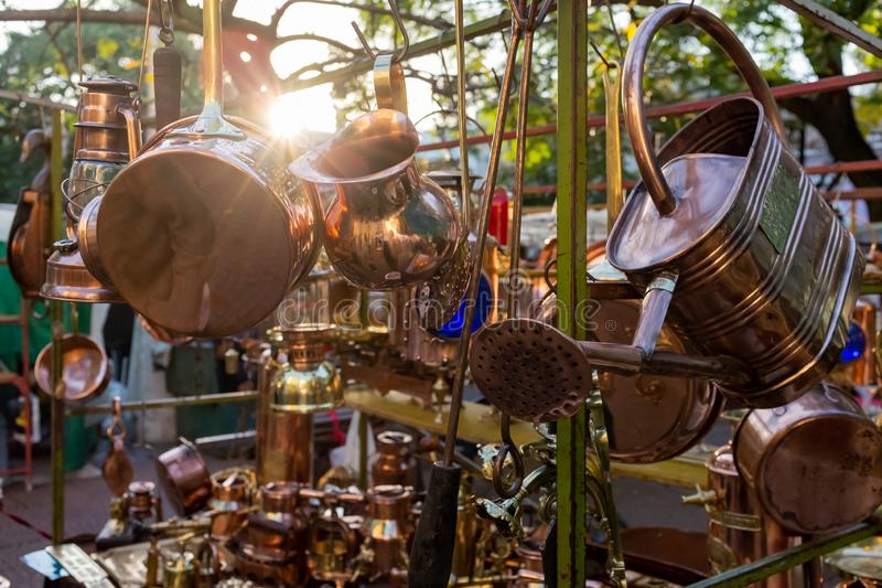 Vintage brass saucepans, jugs and watering can on a market stall at flea market in San Telmo, Argentina, South America royalty free stock images