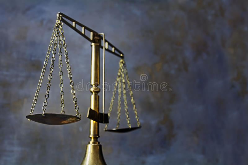 Vintage brass scales of justice against a dark rustic background. Vintage brass scales in threatening lighting against a dark rustic background, concept for stock images