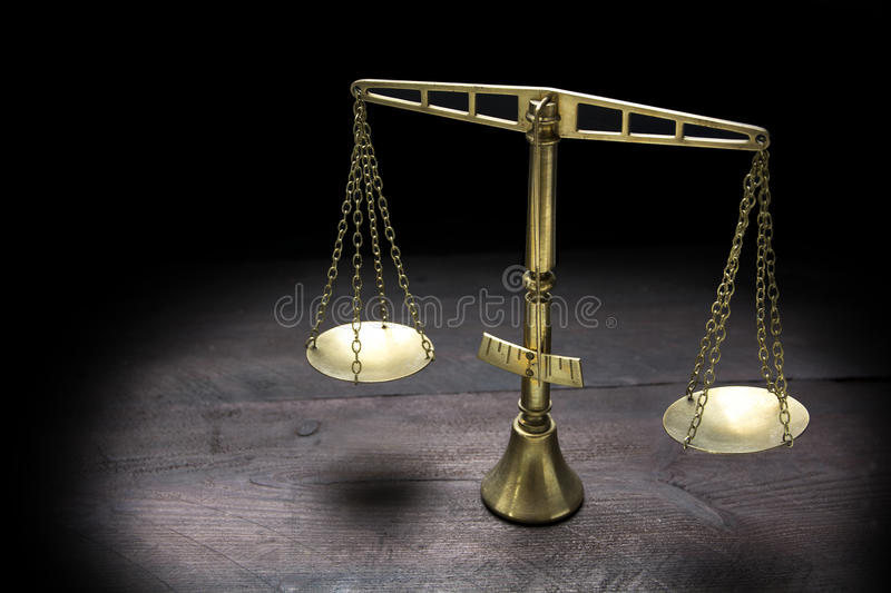 Vintage brass scales of justice in spotlight against a black bac. Vintage brass scales of justice in spotlight on dark wood against a black background, selected royalty free stock photography