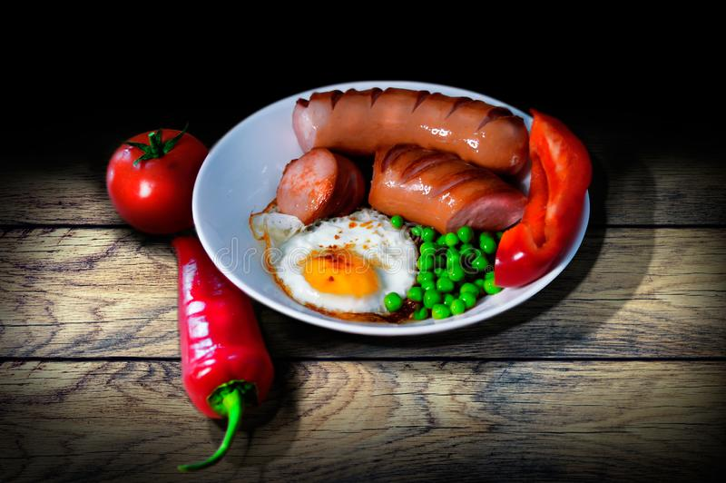 Vintage breakfast on wooden table. Of fried peas and peas sausages pepper and tomato stock image