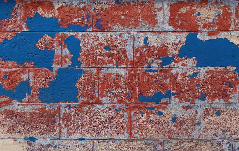 Vintage brick wall background. Brick texture with several layers of peeled paint. Old crumbling wall. stock image