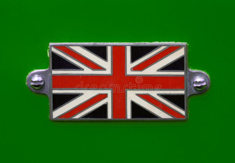 Vintage British Union Jack flag badge on a racing green coloured car close up. A Vintage British Union Jack flag badge on a racing green coloured car in close up royalty free stock photography