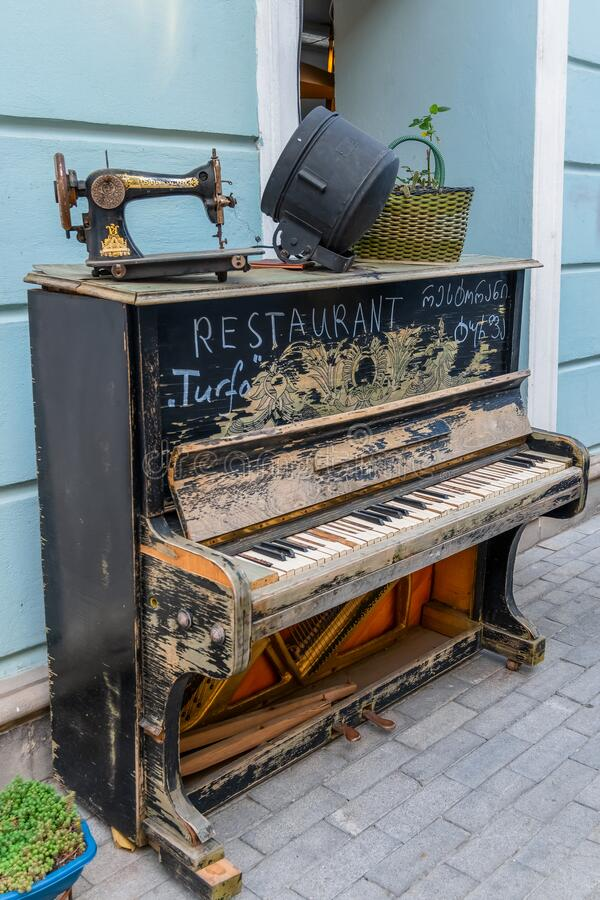 Tbilisi, Georgia, 16 December 2019 -  vintage broken piano and sewing machine advertising of restaurant  on a pedestrian street stock photography