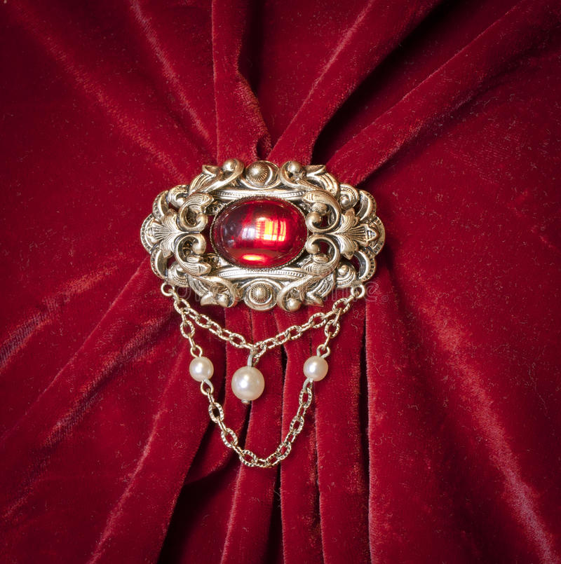 Vintage brooch. Antique brooch on a red velvet royalty free stock photo