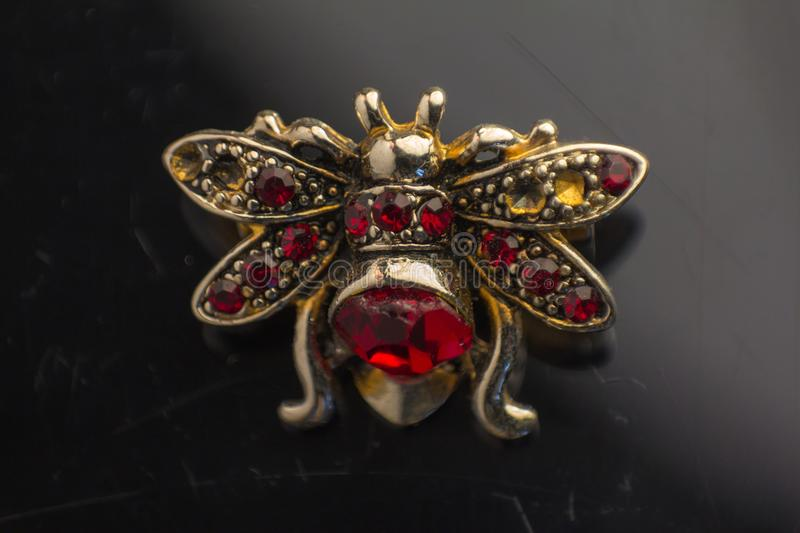 Vintage brooch in the form of bees made of beads, fabric and crystals, clipping on a old black background stock photos