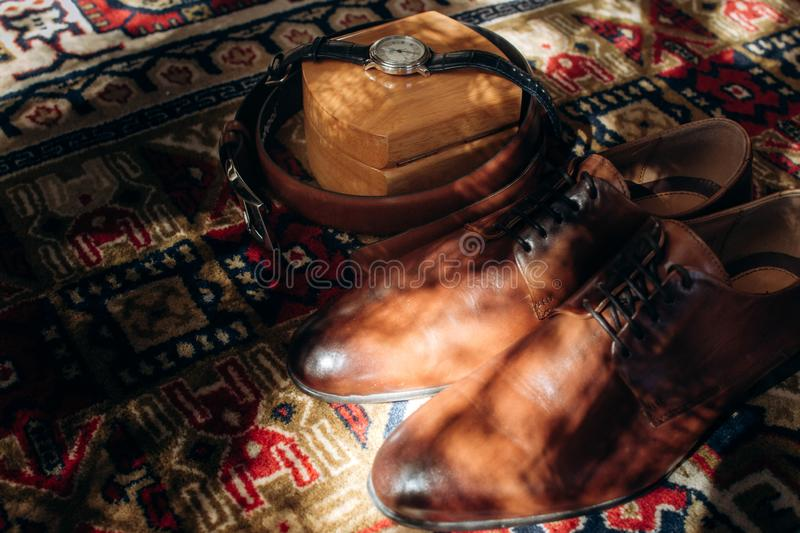 Vintage brown leather shoes near elegant black watch and leather top view closeup, groom accessories for wedding ceremony concept royalty free stock photography