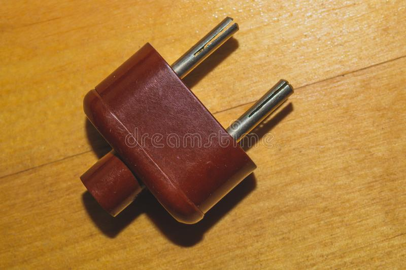 Vintage brown power plug without cord on the wooden background royalty free stock photography