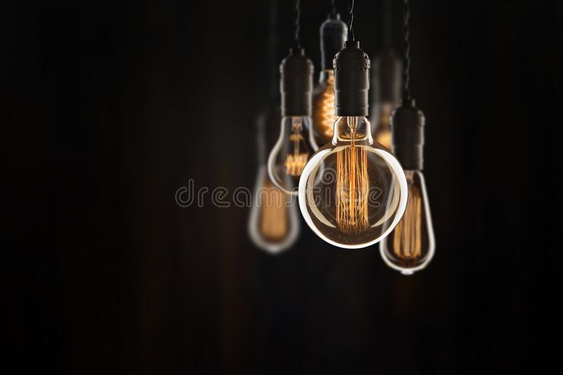 Vintage bulbs on black background - idea, innovation, teamwork and leadership concept. Space for text. Idea and leadership concept Vintage bulbs on wall stock photography