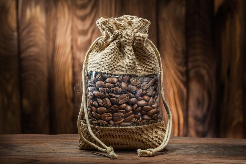 Vintage burlap bag with coffee beans on old wooden background royalty free stock photography