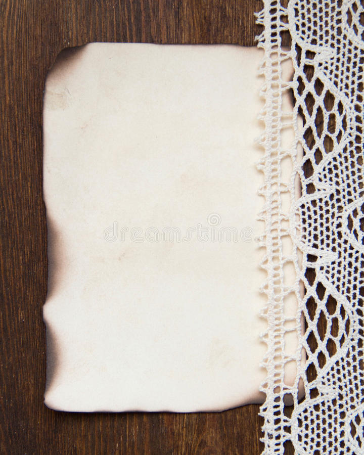 Vintage burned paper card and crochet lace stock photography