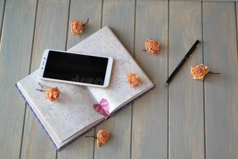 Vintage business image: mobile, pen, notepad and roses on a pastel blue table. Composing in the life style for design. top. flatly. Vintage business image stock photo