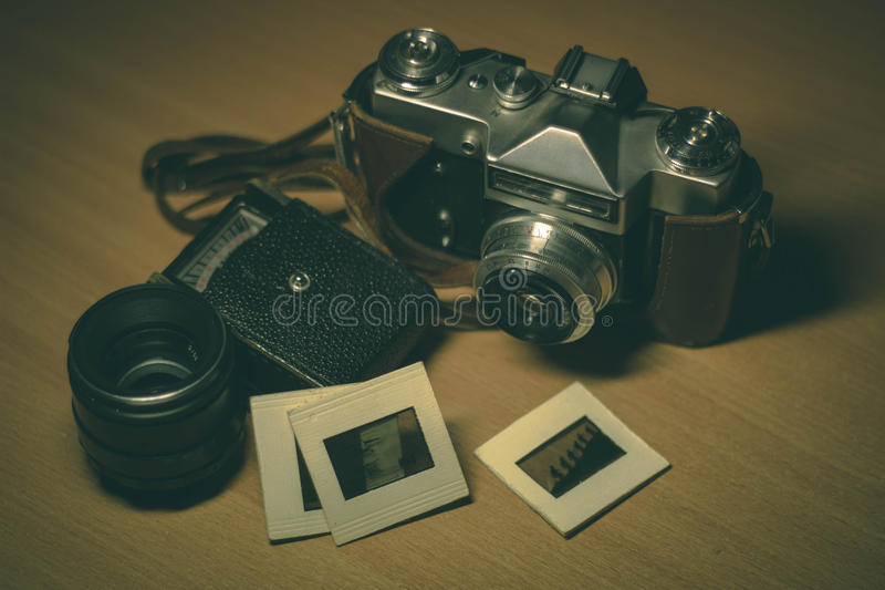 Vintage camera and accessories. Old camera, exposure meter, old lens and photo slides stock image
