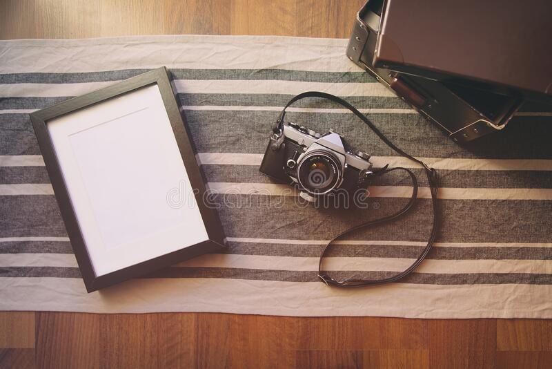 Vintage camera and blank photo frame on wooden table. stock images