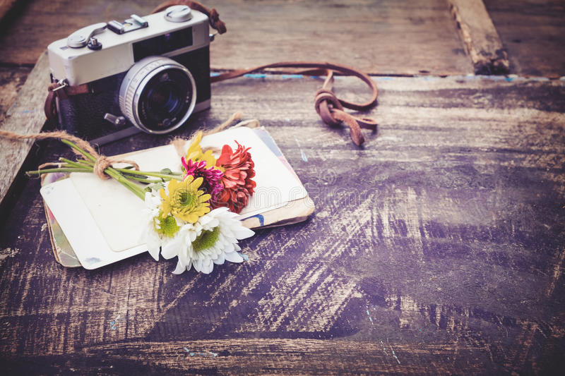 Vintage camera with bouquet of flowers on old wood background royalty free stock photos