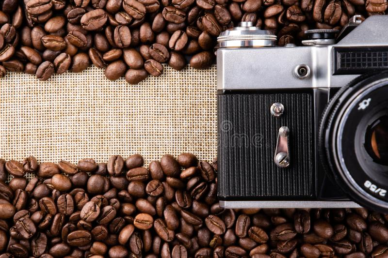 Vintage camera and coffee beans on burlap with copyspace royalty free stock photography