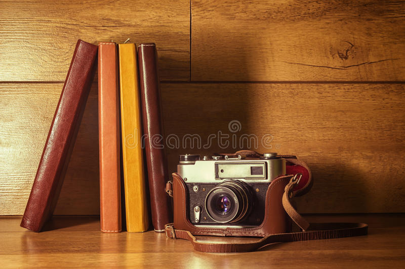 Vintage camera. Vintage film camera with a leather case and a few books royalty free stock image