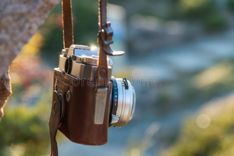 Vintage camera. Hangs on rock at sunny day royalty free stock photography