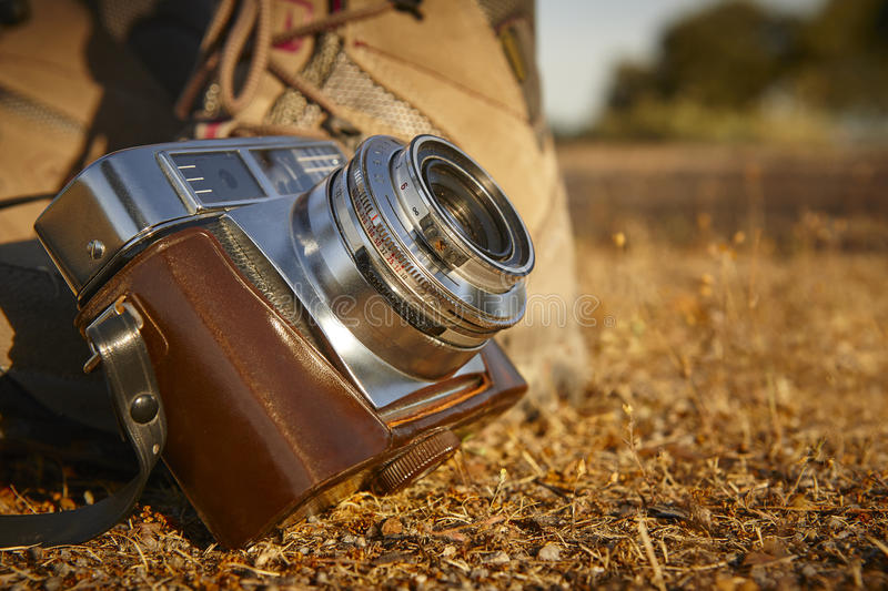 Vintage camera with hiking boots on the ground. Travel stock photography
