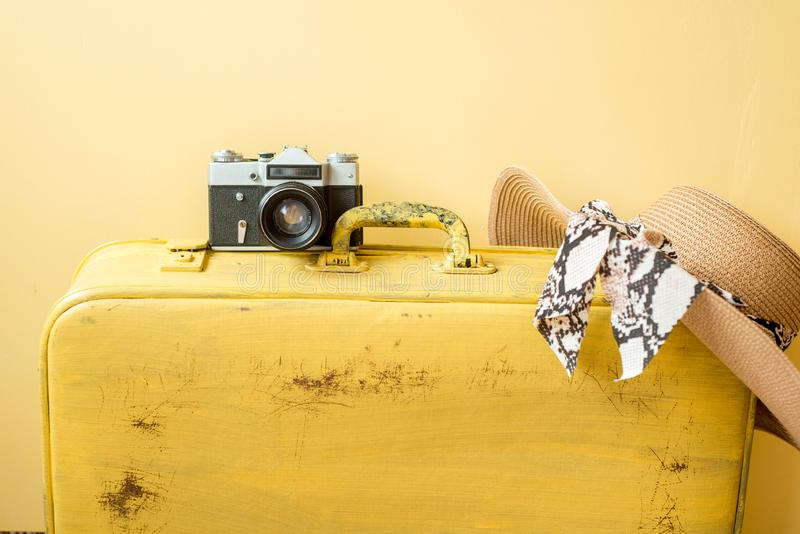Vintage camera and old bright yellow suitcase. straw hat on a yellow background. Travel and summer vacation concept. Flat lay,top. View, copy space stock photo