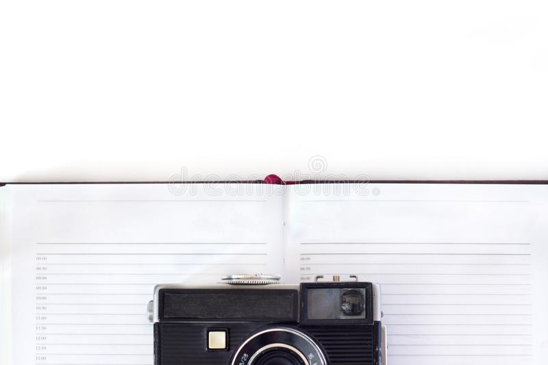 Vintage camera with strap and book on white background, top view . royalty free stock photos