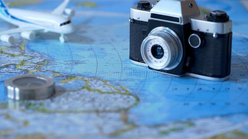 Vintage camera and toy plane on world map background, planning of vacations royalty free stock image