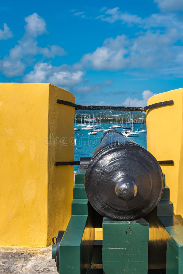Vintage cannon through the turret facing the sailboats in the Ca stock photography
