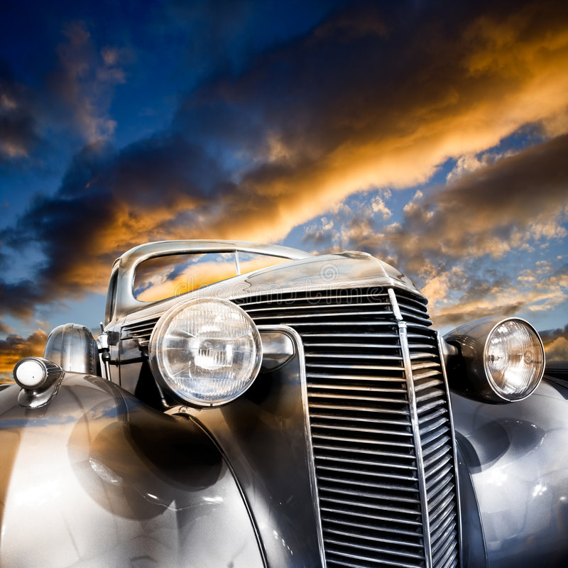 Vintage Car. Front-view of silver colored vintage car bonnet, under a colorful sky in the evening