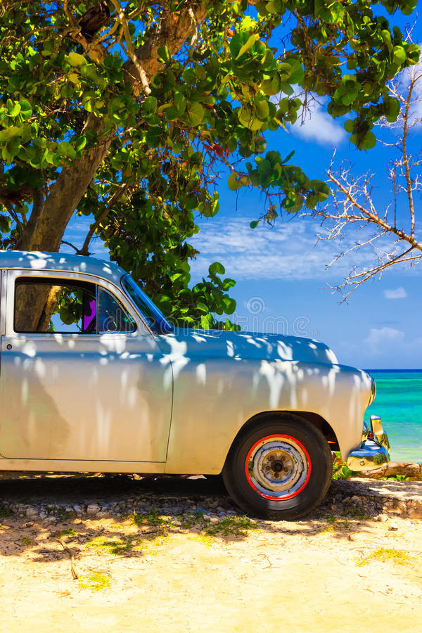 Vintage car at a beach in Cuba royalty free stock images