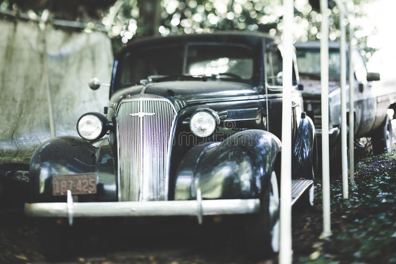 Vintage car in car port. A classic, antique, black car parked under a home car port stock photography