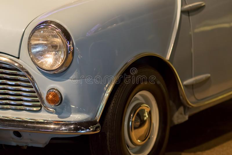 Vintage car. Classic 1960s British car in close-up. Headlight and front wing of a pale blue small automobile. Retro headlamp detail stock images