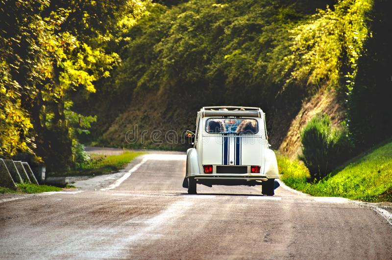 Vintage car country winding road back view friends road trip stock photos