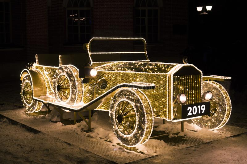 Vintage car of glowing Christmas lights. On snow stock photo